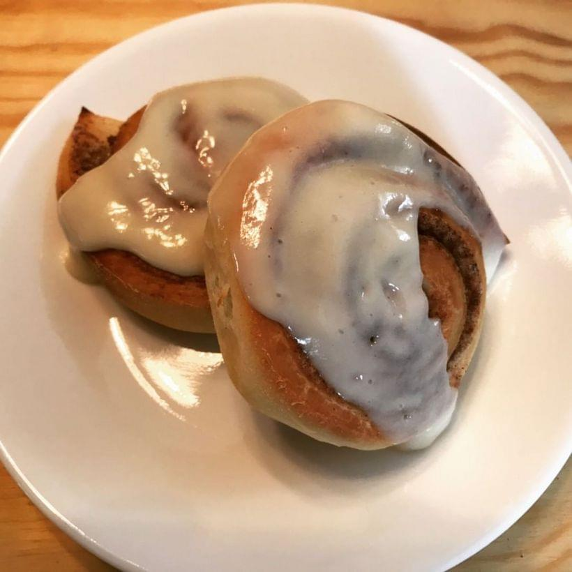Two spiraled cinnamon buns on a small plate, covered in icing.