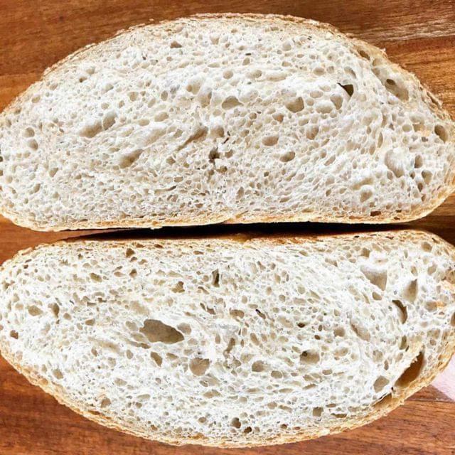 A cross-section of a sourdough boule, highlighting the irregular, open crumb structure.