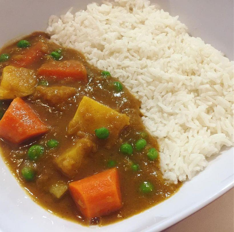 Carrots, peas, and potatoes in a pool of brown curry sauce, served on a bed of white rice.