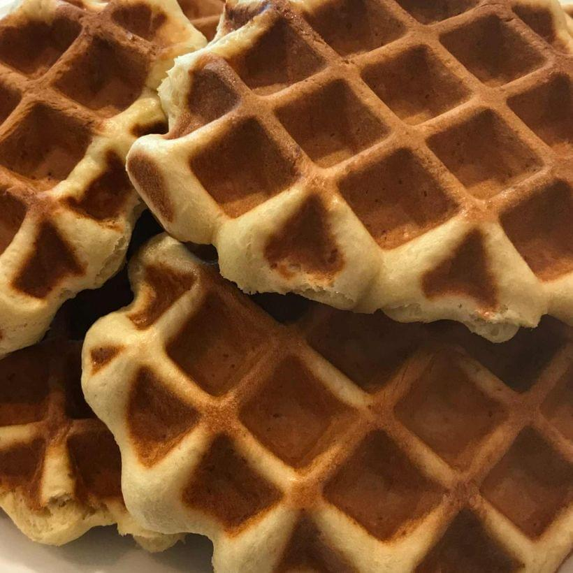 A stack of dark, chestnut brown waffles.