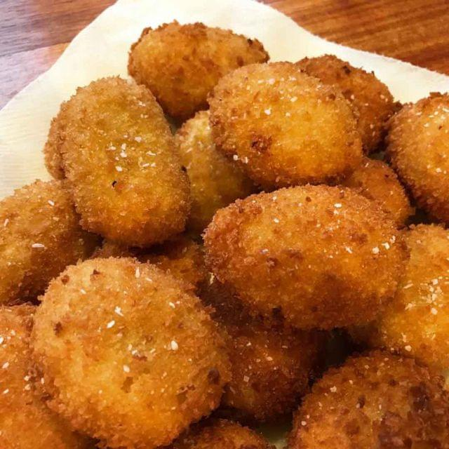 A pile of golden brown croquettes, dusted with salt.