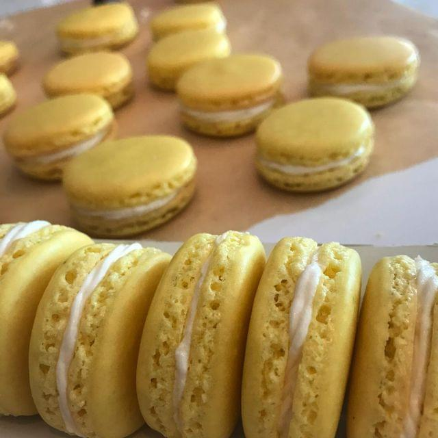 Bright yellow macarons with white buttercream filling, on a sheet of parchment paper.
