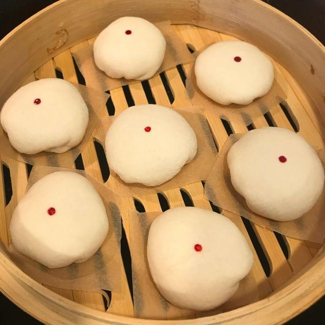 A handful of small, round, white dumplings, each with single red dot on the top, inside of a bamboo steamer basket.