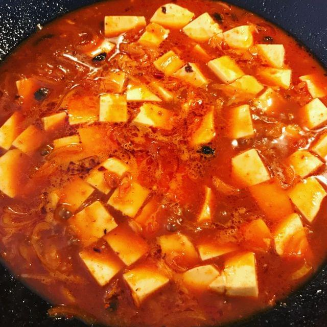 A wok containing cubes of tofu simmering in a fiery red sauce.