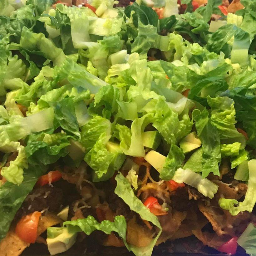 A close-up of a tray of nachos, piled—perhaps to excess—with meat, beans, lettuce, tomatoes, and red peppers.
