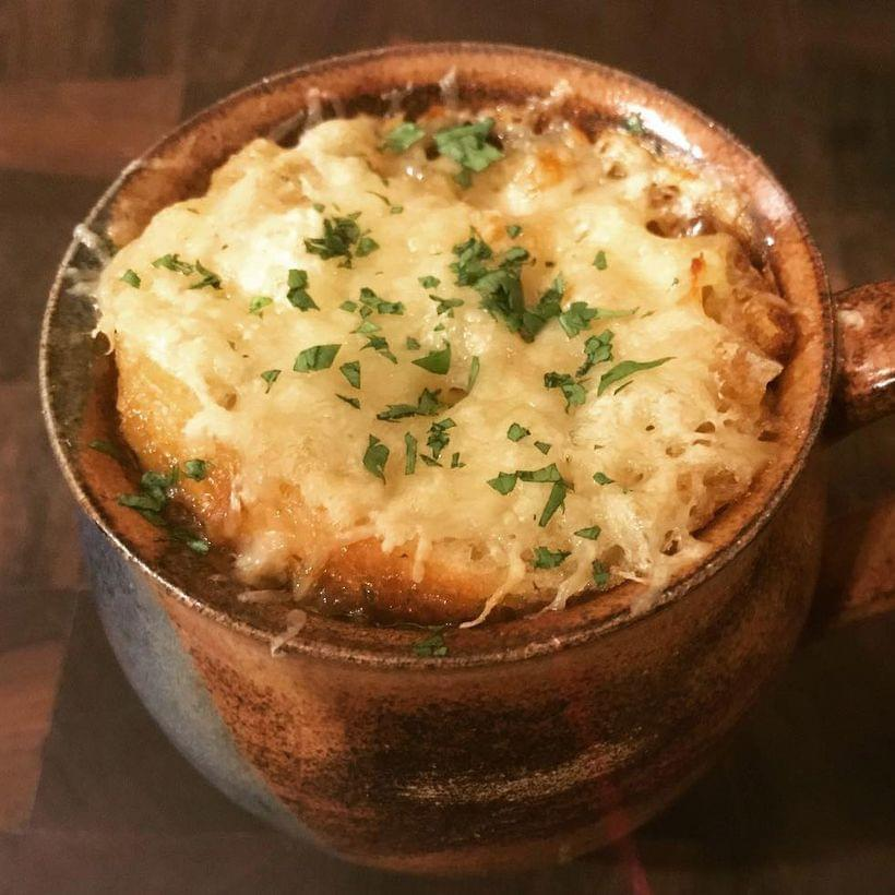 An earthenware mug of french onion soup, topped with a sourdough crouton, melted cheese, and a sprinkling of finely chopped parsley