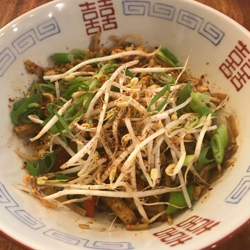 A bowl of dark brown rice noodles, topped with raw bean sprouts and scallion greens.