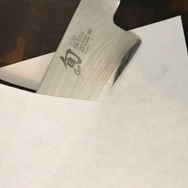 A knife slicing through a sheet of paper.