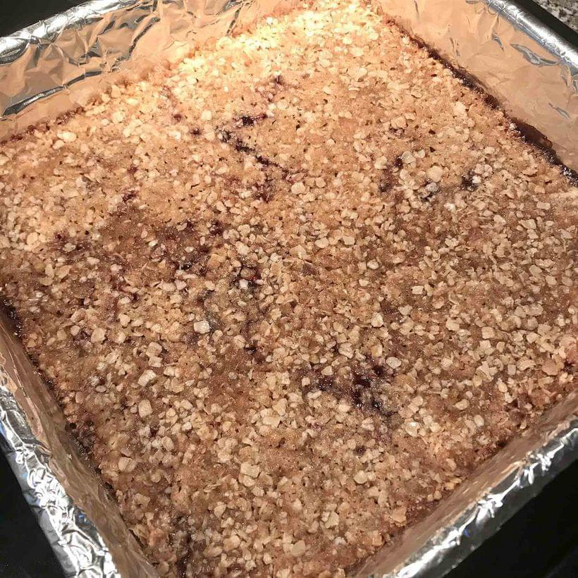 An uncut tray of raspberry bars, with the filling just showing through the topping in places.