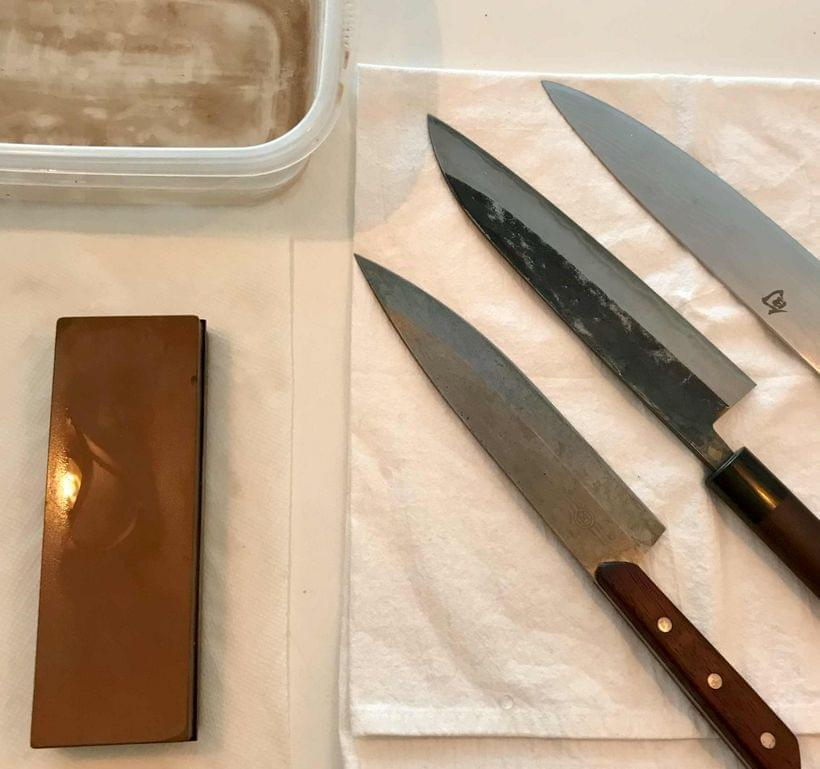 Three chef's knives side-by-side on a cloth rag, alongside a dampened sharpening stone and a bowl of water.