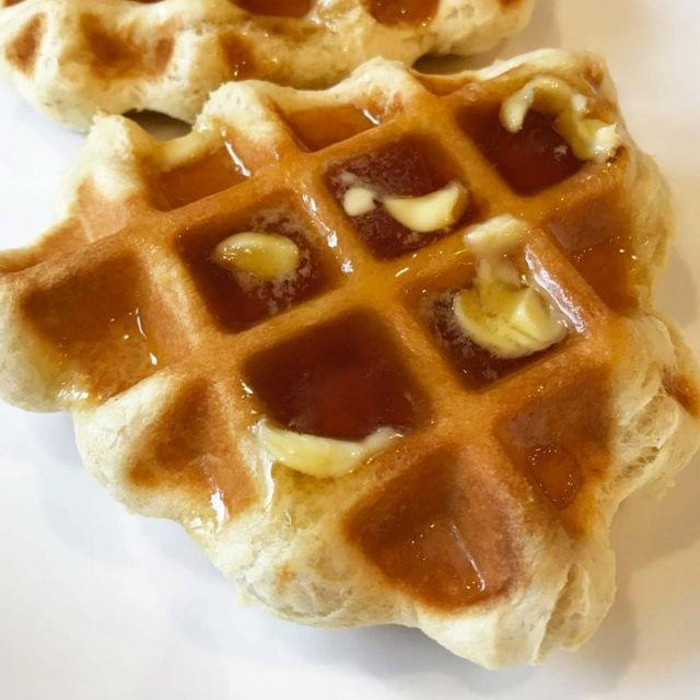 A thick, triangular, golden brown waffle with butter and syrup.