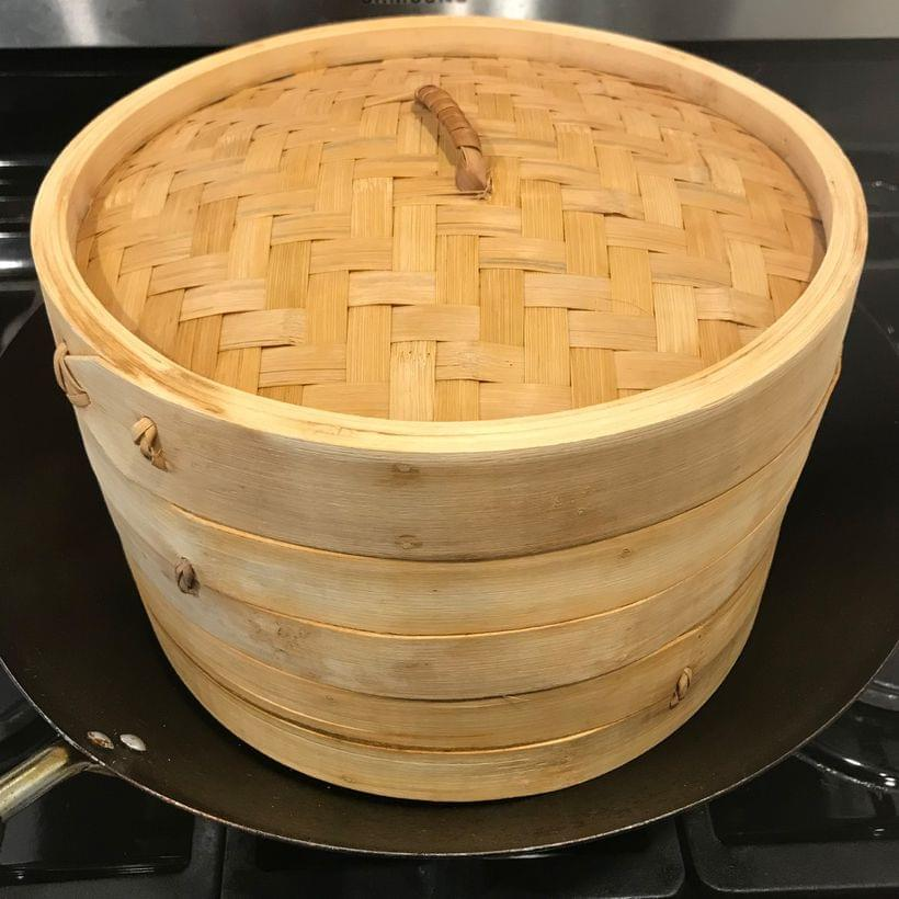 A wok on a stovetop, containing a stack of bamboo steamer baskets.